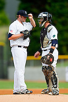 Charlotte Knights catcher Bryan Anderson (33) has a chat on the mound with starting pitcher Stephen McCray (45) during the International League game against the Durham Bulls at Knights Stadium on August 18, 2013 in Fort Mill, South Carolina.  The Bulls defeated the Knights 5-1 in Game Two of a double-header.  (Brian Westerholt/Four Seam Images)