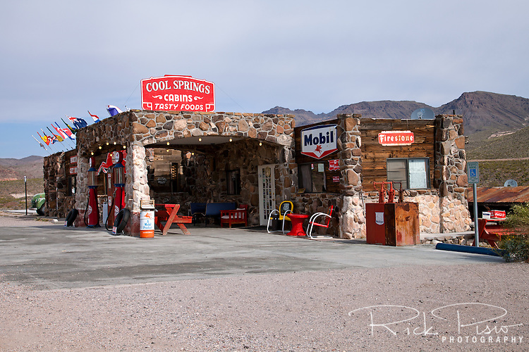Located on the Oatman Road along the original Old Trails Highway offered a respite for travelers heading west over the Black Mountains. Cool Springs first opened in the mid 1920's and operated until the realignment of Route 66 in the 1950's slowed traffic on the old route to a trickle. In the mid-sixties a fire burned Cool Springs to the ground leaving nothing but fragments of the stone foundations and the original stone pillars. <br /> <br /> In 1991 the building was temporarily rebuilt as part of the set for the Jean-Claude Van Damme and Dolph Lungren action movie &quot;Universal Soldier&quot; before being blown up at the end of the scenes that were filmed there. <br /> <br /> In 2001 Ned Leuchtner purchased the site from the niece of Floyd Spidell, the last owner prior to the fire in the 1960's, and began a  restoration project to bring Cool Springs back to its former glory. Recently the cafe was rebuilt and opened as a museum that features nearly every Rolling Stones album, with autographs!