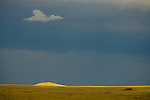 Sunlight hits a distant hill as a storm breaks over the high plains of Wyoming