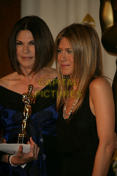 COLLEEN ATWOOD & JENNIFER ANISTON.The 78th Annual Academy Awards - Press Room, held at the Kodak Theatre, Los Angeles, California, USA. .March 5th, 2006.Photo: Russ Elliot/Admedia/Capital Pictures.Ref: RE/ADM.Oscar Oscars half length award trophy blue black off the shoulder dress black.www.capitalpictures.com.sales@capitalpictures.com.© Capital Pictures.