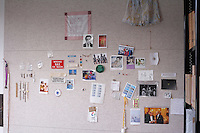 Arrangement of photographs and other items on display on pinboard