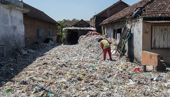 21 May 2019, Bangun Village,East Java, Indonesia: A local man picks through plastic rubbish in Bangun Village outside Surabaya, Indonesia. Millions of tonnes of recyclable plastic trash from Australia and Europe is dumped for rag pickers to separate and sort. The plastics are used to fuel fires at local tofu factories among other industries. Australia is illegally sending non recyclable trash hidden within this lode and the Indonesian Government is cracking down on the practice and preparing to refuse to take Australia's rubbish that is creating environmental and health issues locally. Picture by Graham Crouch/The Australian