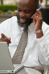 Happy African American man with laptop and talking on cell phone