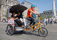 Toeristen in een fietstaxi in Amsterdam