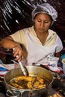 Oaxaca, Mexico, North America.  Day of the Dead Celebrations.  Young Woman Cooking Bananas outside entrance to San Miguel Cemetery.  Visits to the Cemetery take on a carnival, family atmosphere as parents treat their children to sweets, candies, toys, and amusement rides.