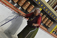 An old nun performs the kora around the monastery at the refugee camp location on the outskirts of Kathmandu, Nepal