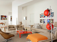 A contemporary living room in neutral tones. A Suita sofa and armchairs designed by Antonio Citterio for Vitra, form a quiet seating area within the open plan room. A bold orange coffee table and a vibrant paintings by Franzisca Maderthaner brings colour to the otherwise neutral room.