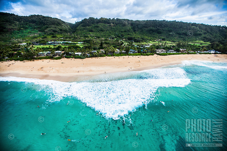An aerial view of surfers catching a big wave on O'ahu's North Shore.