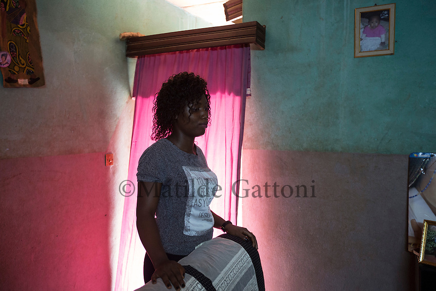 "Cameroon - Yaoundé - Emilia Ngabi, 21, stands in her uncle's living room where she has been living since both her parents passed away. In January 2015, Leonge, her 35 years olf brother left for Europe. ""I implored him to come back so many times, but he said he couldn't. He was determined to go"". In May 2016, Leonge called her sister one last time from Libya, telling her he would try to cross in the following days and that he would call back once he had reached Italy. That was the last time Ngabi heard his voice. Then, on the 24th of May, at 11.30pm, Ngabi saw a friend posting a message on his brother's Facebook page. It read ""rest in peace."""