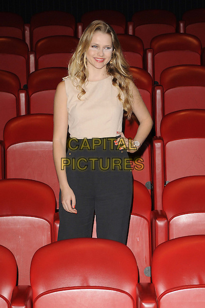"""Teresa Palmer.attended the photocall to celebrate the release of the zom-rom-com """"Warm Bodies"""", Soho Hotel, Richmond Mews, London, England, UK, .18th January 2013..half length  cinema beige black sleeveless hand on hip catsuit trousers high waisted  .CAP/CAN.©Can Nguyen/Capital Pictures."""