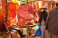 Fresh yak meat is offerred at a butcher's stall in a Tibetan outdoor market.