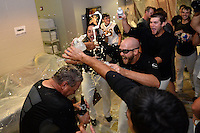 Jacksonville Suns douse pitching coach John Duffy (13) in the locker room after game three of the Southern League Championship Series against the Chattanooga Lookouts on September 12, 2014 at Bragan Field in Jacksonville, Florida.  Jacksonville defeated Chattanooga 6-1 to sweep three games to none.  (Mike Janes/Four Seam Images)