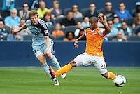 Jacob Peterson (37) Sporting KC crosses the ball in front of Corey Ashe (26) defender Houston Dynamo ..Sporting Kansas City and Houston Dynamo played to a 1-1 tie at Sporting Park, Kansas City, Kansas.