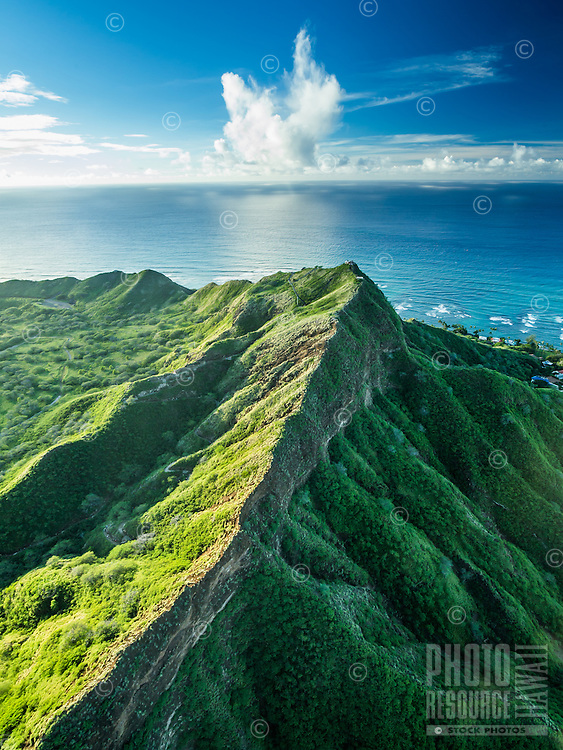 An aerial view of the summit of O'ahu's Diamond Head, with clouds shaped like wings over the horizon.