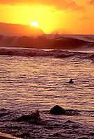 A surfer heads out for a final set as the sun sets at Kaena Point on the north shore of Oahu.
