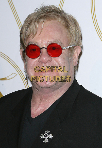 "Sir Elton John.LoveGold and Elton John Aids Foundation Celebrate Documentary ""How To Survive a Plague"" held at Chateau Marmont, Los Angeles, California, USA, 22nd February 2013..portrait headshot glasses earring tinted round cross brooch  black red sunglasses .CAP/ADM.©AdMedia/Capital Pictures."