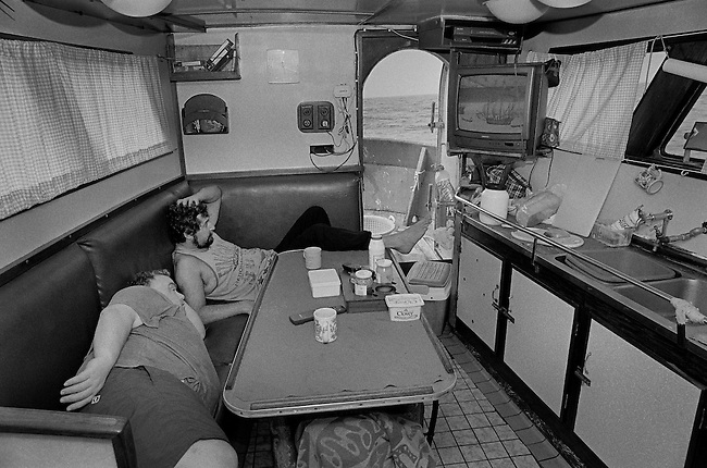 PZ 198, the 'Aaltje Adriaantje'.<br /> Richard and Malcolm watching television in the galley.<br /> <br /> <br /> These boats are out for seven days at a time in all weathers and the nets are hauled up every three hours around the clock. The crew consists of five self-employed fishermen who share the profits of the catch.