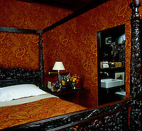 The walls, curtains and carved four-poster bed in this bedroom are dressed in an orange paisley fabric
