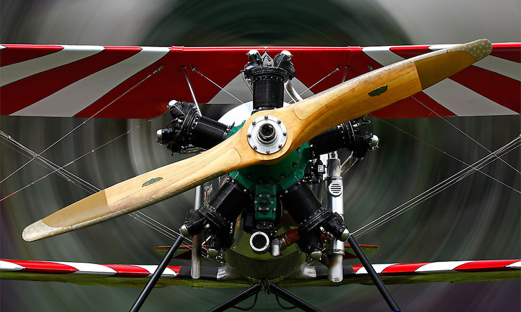 Photographed directly facing a 1939 Meyers OTW (out-to-win) bi-plane featuring the green and black Kinner Radial Engine, the wooden propeller and the wire struts of the the red-and-white-striped wings against a swirling, background camouflaging the activity at the 2010 Wings 'n' Wheels Showcase. Selected for Photographic Center - Capital District - Best of 2010 Exibition.