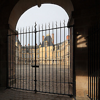 Gates leading to the Cour Ovale, the central courtyard from which 16th and 17th century facades spread out from the original keep, Chateau de Fontainebleau, France. The Palace of Fontainebleau is one of the largest French royal palaces and was begun in the early 16th century for Francois I. It was listed as a UNESCO World Heritage Site in 1981. Picture by Manuel Cohen