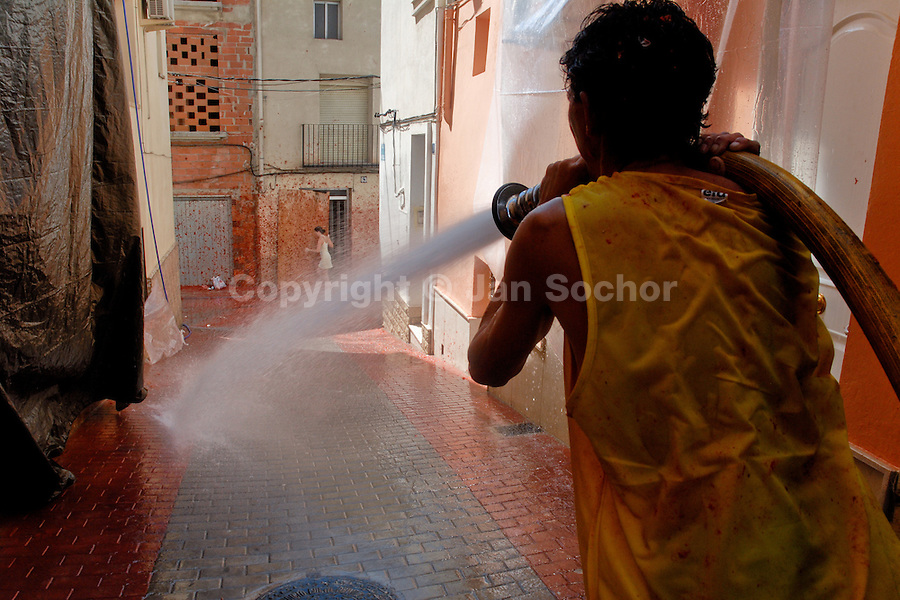 A Spanish man cleans the street with a water hose after La Tomatina festival in Bunol, Spain, 31 August 2006. La Tomatina is a tomato fight held annually in the town of Bunol, close to Valencia. Approximately 40,000 people from all over the world arrive to fight in the battle in which about 50 tons of over-ripe tomatoes are thrown in the street. During the one hour battle everybody fights everybody by throwing squashed tomatoes. The origin of this event is unknown but the Tomatina fights have been recorded since 1945.