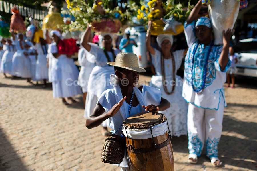 A young Candomblé follower plays drum during the ritual procession in honor to Yemanjá, the goddess of the sea, in Amoreiras, Bahia, Brazil, 3 February 2012. Yemanjá, originally from the ancient Yoruba mythology, is one of the most popular ?orixás?, the deities from the Afro-Brazilian religion of Candomblé. Every year on February 3rd, hundreds of Yemanjá devotees participate in a colorful celebration in her honor. Faithful, usually dressed in the traditional white, gather at the beach on Itaparica island to leave offerings for their goddess. Gifts for Yemanjá include flowers, perfumes or jewelry. Dancing in the circle and singing ancestral Yoruba prayers, sometimes the followers enter into a trance and become possessed by the spirits. Although Yemanjá is widely worshipped throughout Latin America, including south of Brazil, Uruguay, Cuba or Haiti, the most popular cult is maintained in Bahia, Brazil.