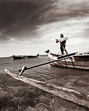 MADAGASCAR, Nosy Komba, Jardin Vanille, boy holding a Travali fish standing on an outrigger canoe, Indian  Ocean