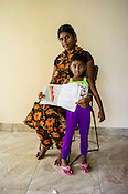 A Sri Lankan woman poses for a photo with her cousin and the CHDR- Child Health Development Record Card (immunization/vaccination card) in the Ministry of Health office in Tharmapuram Village in Kilonochchi, Sri Lanka.  Photo: Sanjit Das/Panos