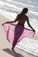 A young woman with a sarong at the beach at Makena, Maui.