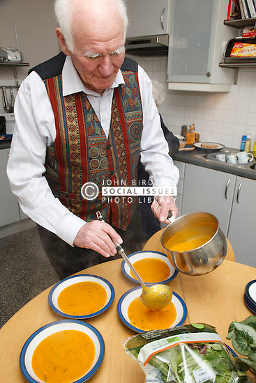 Elderly man serving soup.