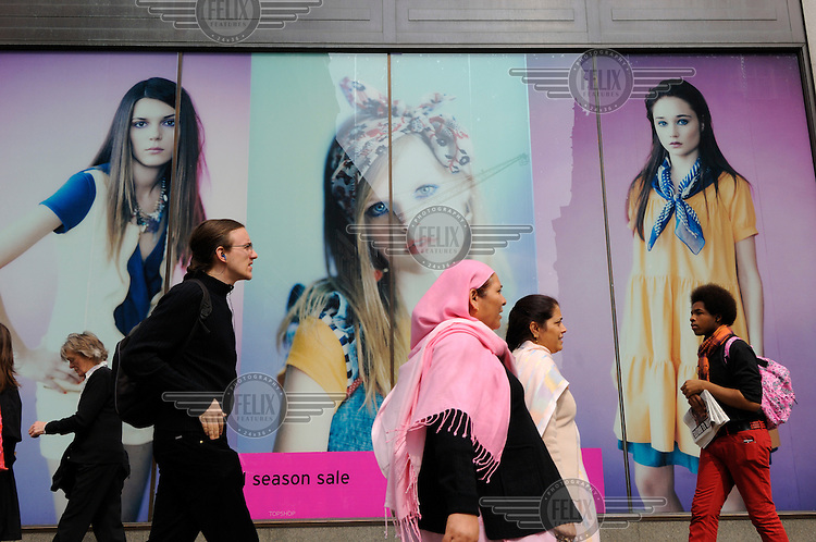 Multi ethnic shoppers passing fashion adverts using young models on an Oxford Street retailer's sale poster in London.