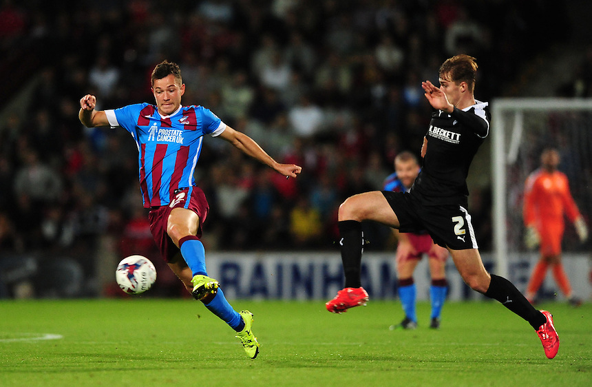 Scunthorpe United's Tom Hopper vies for possession with Barnsley's James Bree<br /> <br /> Photographer Chris Vaughan/CameraSport<br /> <br /> Football - Capital One Cup First Round - Scunthorpe United v Barnsley - Tuesday 11th August 2015 - Glanford Park - Scunthorpe<br />  <br /> &copy; CameraSport - 43 Linden Ave. Countesthorpe. Leicester. England. LE8 5PG - Tel: +44 (0) 116 277 4147 - admin@camerasport.com - www.camerasport.com