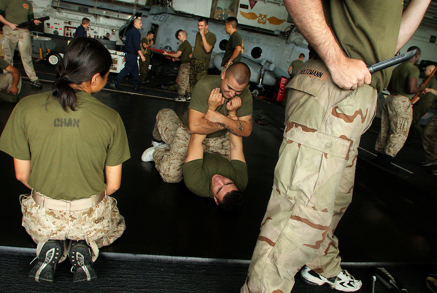 Students taking part in the Marine Corps Martial Arts Program (or MCMAP) go over grappling techniques and weapons manipulation in the Belleau-Wood's hangar bay as they train for a new belt.  MCMAP, which was formalized in 2000, incorporates techniques from a wide variety of fighting forms with an emphasis on the use pinning techniques and weapons in hand-to-hand combat.