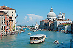 Vaporatto (buses) on the Grand Canal, basillica Santa Maria Della Salute in the background, Venice, Italy