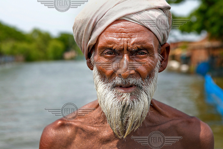 A man whose house was destroyed by flood waters that have innundated the Satkhira District. Each year limited flooding helps to enrich the soil and create very fertile farm land. In turn, this results in a high population density on the flood plain. However, the low lying land is also prone to extreme flooding events that are very destructive to both the economy and human life.