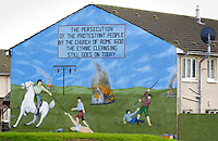 Protest mural depicts struggle between Protestants and Catholics  and ethnic cleansing painted on house wall in Belfast, Northern Ireland