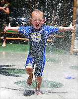 V.Summer.1.0520.jl.jpg/photo jamie Scott Lytle/three year old Wade Carroll of Carmel Mountian runs through the water spray at The Wave Waterpark in Vista Wednesday enjoying summer one day early.