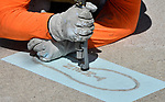 "Pete Milton, a foreman from the Bazan Painting Company in Olivette, uses sandblasting equipment to etch the word ""then"" into one of 20 concrete sidewalk slabs leading to the area where the statue of Robert Wadlow - the ""Alton Giant"" - is displayed in Alton, Illinois. Small pieces of sand are shot at about 50 psi (pounds per square inch) onto the concrete. The rectangular rubberized template outlines the area that will be sandblasted.  The footsteps are a size 37, which was Wadlow's shoe size and are spaced to approximate the gait of Wadlow walking. The visual literary art piece, in the 2800 block of College Avenue, is the brainchild of Aaron Williams, founder and champion of the 7th Grade Poetry Foundation based in St. Louis. Work was being done on Thursday April 26, 2018."