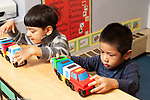 Education preschool 3 year olds two boys playing side by side with toy trucks