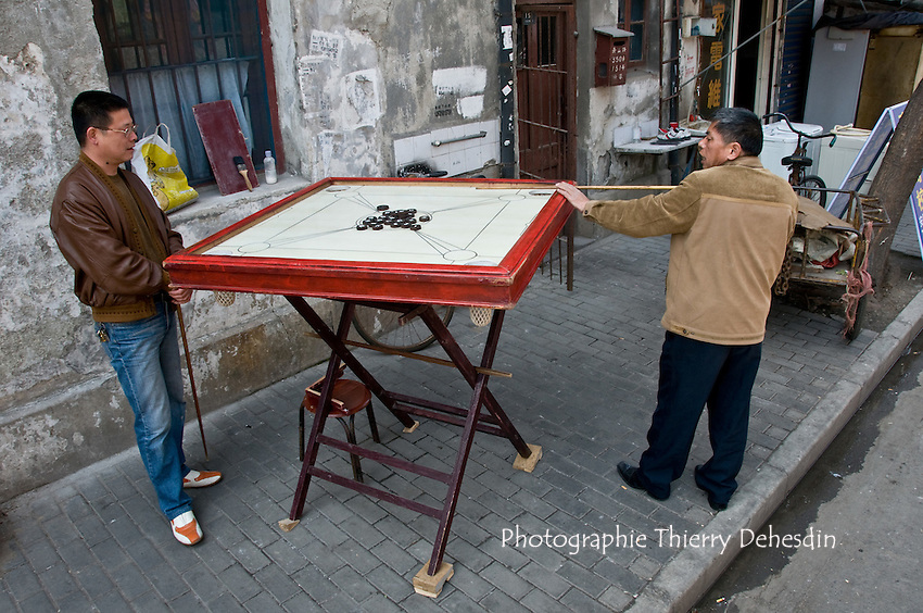 Asia, China, Shanghai (March 2008)..Two friends playing Carrom with Cue sticks and checker pieces on a table board on a Yangpu district street.