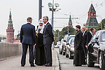 An aide, left, talks with Kirill I, patriarch of the Russian Orthodox Church, and Moscow Mayor Sergei S. Sobyanin during a campaign appearance on a sidewalk between the Kremlin walls and the Moscow River on Thursday, August 29, 2013 in Moscow, Russia.