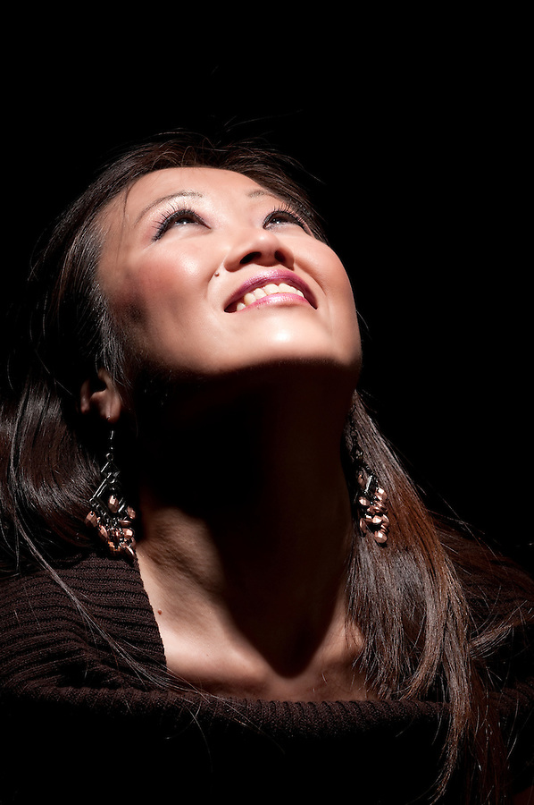 Portrait of cheerful asiatic woman, looking up.