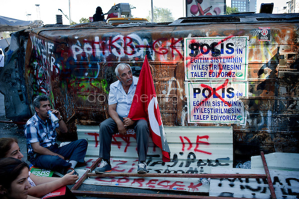 Copyright : Magali Corouge /Documentography<br />Istanbul, Turkey, the 9th of June 2013.<br /><br />A man is sitting near a burned truck not far from Taksim Square while holding a Turkish flag with the face of Mustafa Kemal Atatürk, the first president of Turkey.