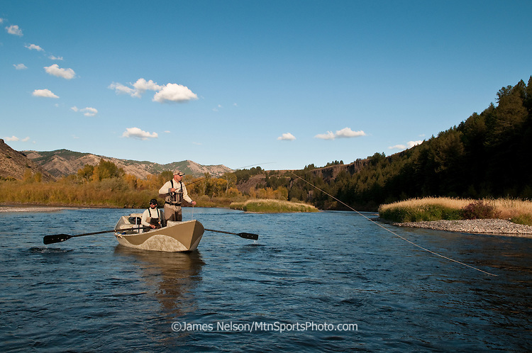 An angler in a drift boat casts a fly for trout on the South Fork of the Snake River, Idaho.