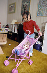 Berkeley CA  Girl, three-years- old, in fantasy play with doll at home