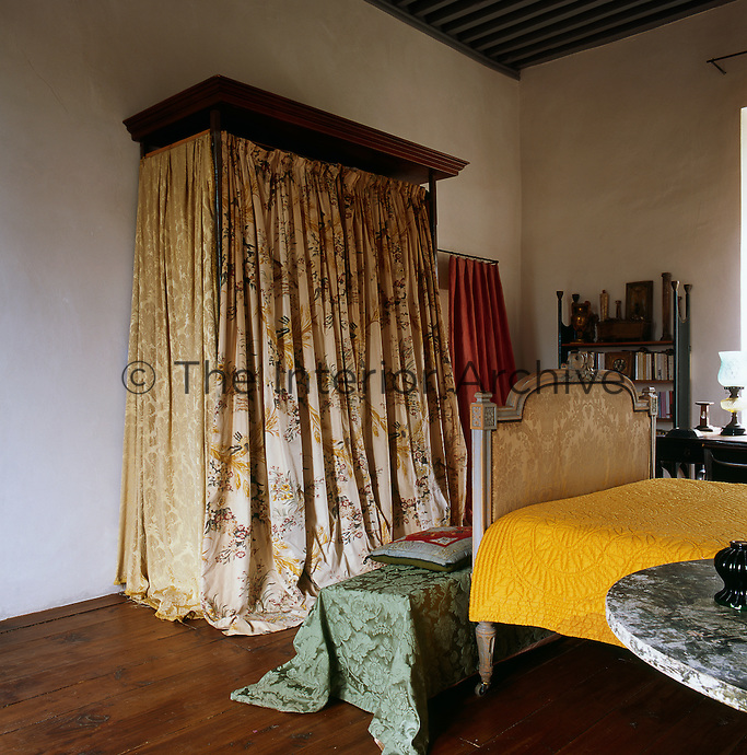 A traditional bed with white painted stone walls and a wooden floor. The room is furnished with an antique bed with a yellow quilted cover and a wardrobe by Giorgio Silvagni.