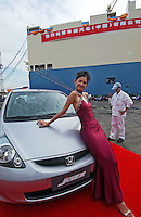A model drapes herself over a newly produced Honda Jazz motor car in Guangzhou, China prior to a ceremony for the first cars exported. Honda Motor Export Plant in Guangzhou, China, produce and export the Honda Jazz model. .