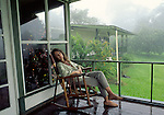 Woman in rocking chair at lodge near Arenal Volcano