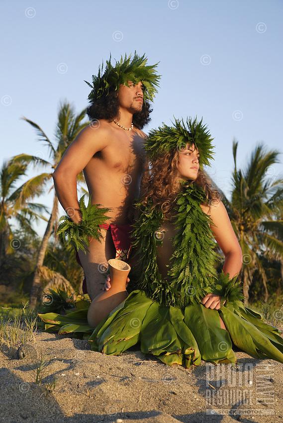 Male (kane) and female (wahine) hula dancers deep in thought, wearing palapalai fern head lei.