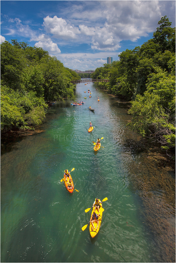 On a warm summer afternoon, Kayakers enjoy the cool waters of Zilker Park and Lady Bird Lake in this photo of life from Austin, Texas.